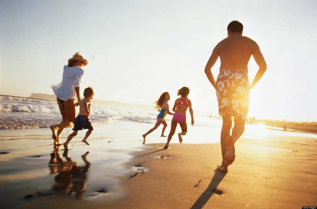 Family running on beach at sunset, rear view