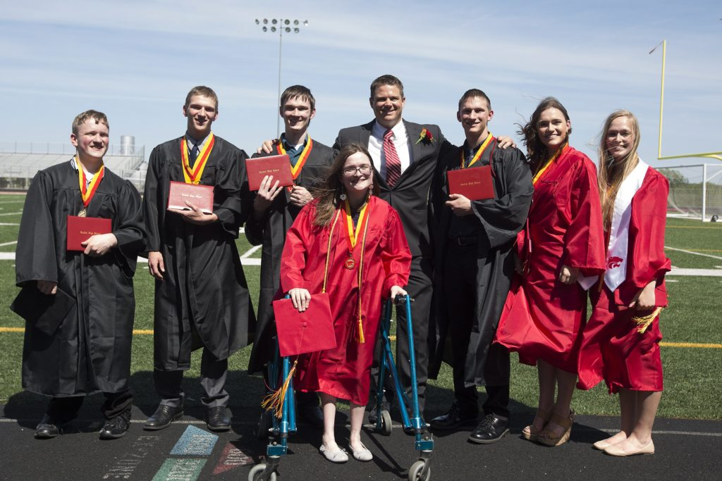 In this Sunday, May 22, 2016 photo, the McCaughey septuplets, the world's first surviving septuplets, from left, Nathan, Kenny Jr., Joel, Alexis, front, Principal Matthew Blackstone, Brandon, Kelsey and Natalie, pose for a picture after graduating from Carlisle High School, in Carlisle, Iowa. (Rachel Mummey/The Des Moines Register via AP) MAGS OUT, TV OUT, NO SALES, MANDATORY CREDIT
